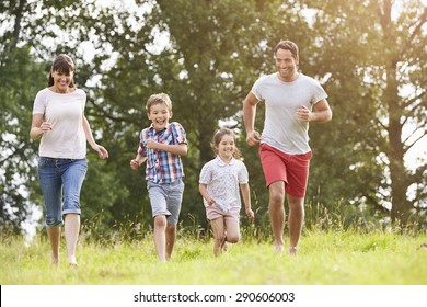 Smiling Family Running Across Summer Field Together