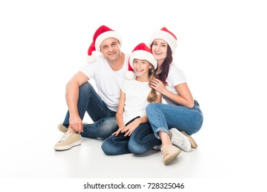 smiling family in Santa hats, isolated on white