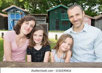 smiling family sit on wood table outdoors front of hut wood village in Bassin Arcachon in France