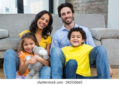 Smiling family sitting on carpet in living room and posing for the camera