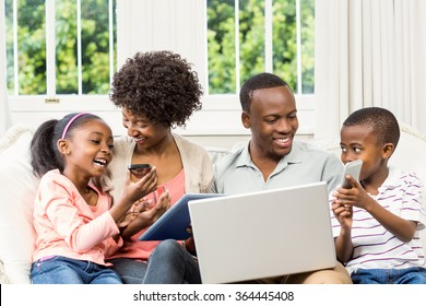 Smiling family sitting on the couch together using laptop and tablet and smartphone