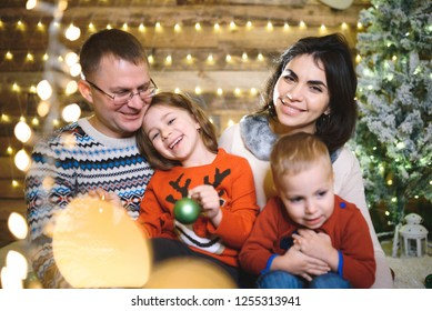 smiling family sitting together in christmas lights