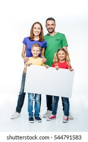 Smiling family standing with blank white card in hands and looking at camera isolated on white