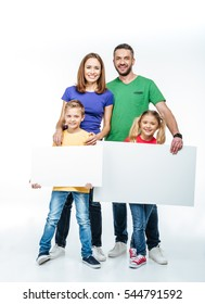 Smiling family standing with blank white cards in hands and looking at camera isolated on white
