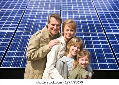 Smiling family standing in front of solar panels