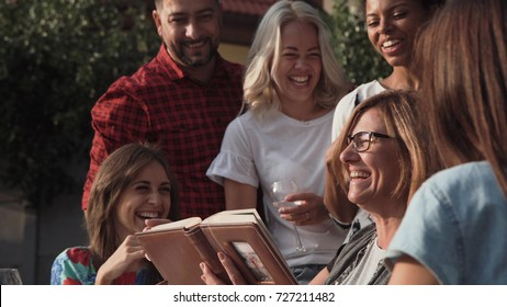 Smiling family standing together while watching photos in album.