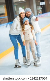 smiling family taking selfie on smartphone on skating rink