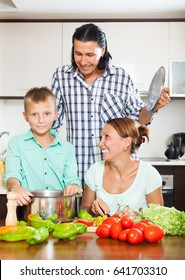 Smiling family with teenager son cooking with fresh vegetables at home kitchen