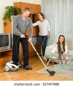 Smiling family of three cleaning at home all together. Focus on man