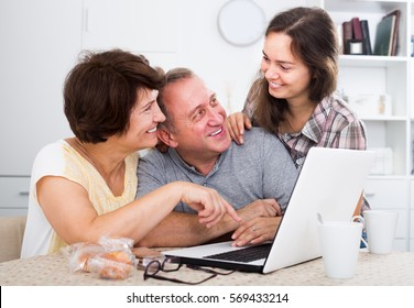 Smiling family of three searching documents on laptop at home