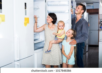 smiling family with two children choosing modern fridge in household store