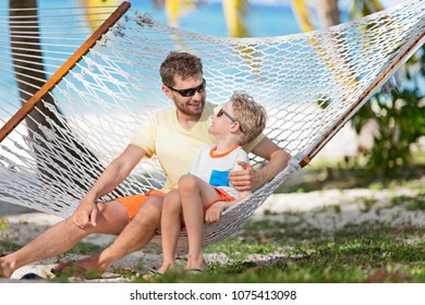 smiling family of two, father and son, enjoying summer tropical vacation together in hammock, father's day concept