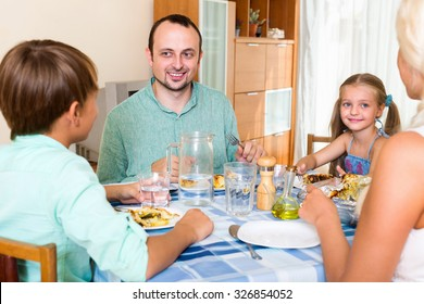 Smiling family with two kids dining together at home