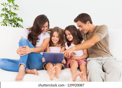 Smiling family using a digital tablet on a sofa