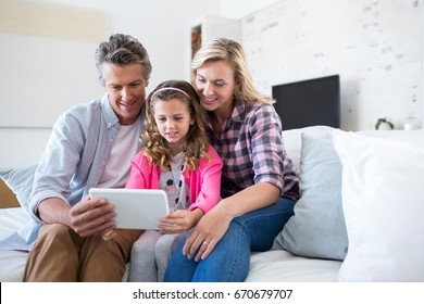 Smiling family using digital tablet together in living room at home