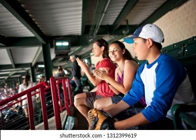 Smiling family watching a baseball game.