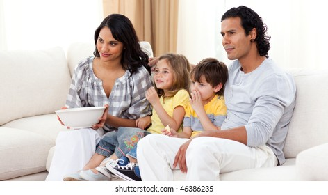 Smiling family watching TV on sofa in the living room