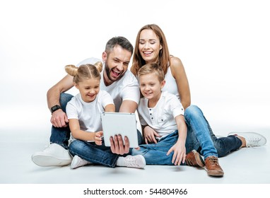 Smiling family in white t-shirts and jeans sitting together and using digital tablet isolated on white