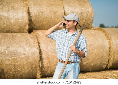 Smiling farmer talking on the phone while in the field