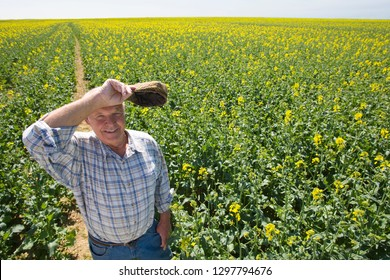 Smiling farmer wiping brow in sunny rape seed field at camera