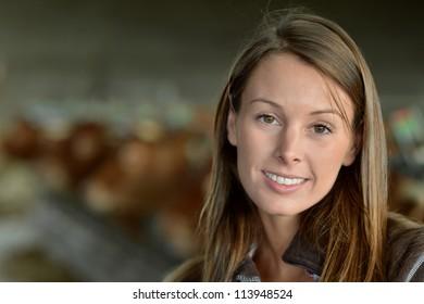 Smiling farmer woman standing in barn