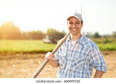 Smiling farmer at work in his field, lens flare effect