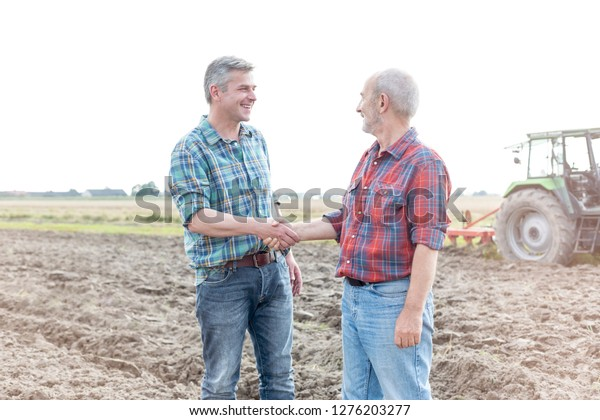 Smiling farmers shaking hands while standing on field at farm