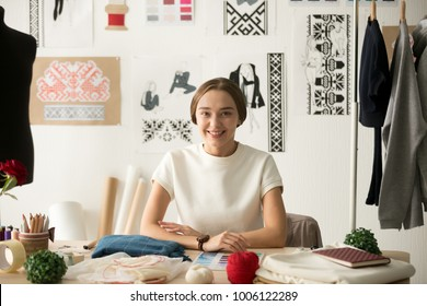 Smiling fashion designer looking at camera at workplace, dressmaker, needlewoman or tailor shop owner sitting at desk with color swatches pantone and embroidery design sketches on the wall, portrait