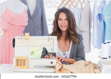 Smiling fashion designer using sewing machine and sitting behind her desk