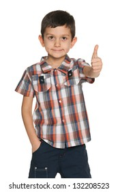 A smiling fashion little boy holding his thumb up on the white background