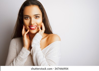 Smiling fashion woman with long hair and red lips posing over white background. Toned in warm colors. Studio shot, horizontal.