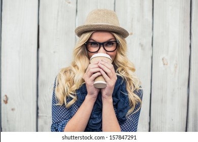 Smiling fashionable blonde drinking coffee outdoors on wooden background