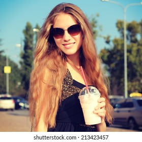 Smiling fashionable blonde drinking a strawberry milkshake outdoors. Photo toned style Instagram filters