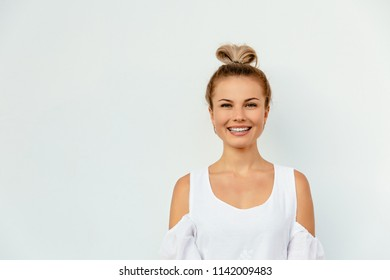 Smiling fashionable girl in white blouse looking at the camera, woman portrait isolated on white background. Copy space