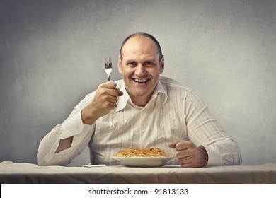 Smiling fat man about to eat spaghetti
