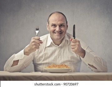 Smiling fat man in front of a plate of spaghetti