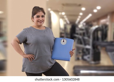 Smiling fat woman in a gym holding a weight scale