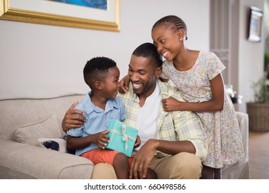 Smiling father and children holding gift box on sofa at home