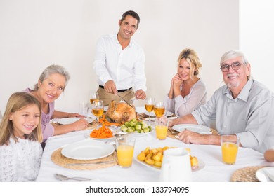 Smiling father cutting slices of turkey for family dinner