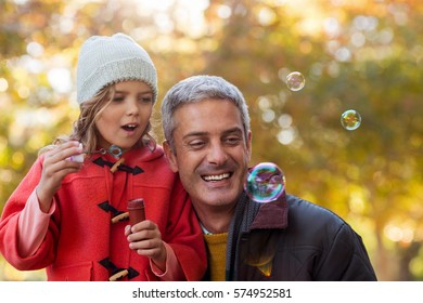 Smiling father with daughter blowing bubbles at park during autumn