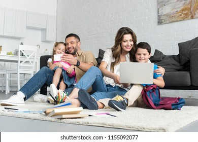 smiling father and daughter taking selfie on smartphone while mother and son using laptop together at home