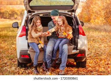 Smiling father with daughters in autumn surroundings