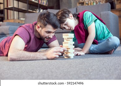smiling father and focused son playing jenga game at home