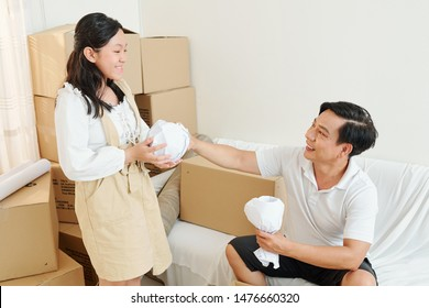 Smiling father giving wrapped glasses and cups to his smiling teenage daughter when they are unpacking in new hosue