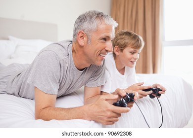 Smiling father and his son playing video games in a bedroom