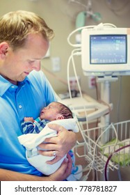 Smiling father holding his newborn baby son in a hospital room