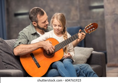 Smiling father and little daughter playing guitar at home