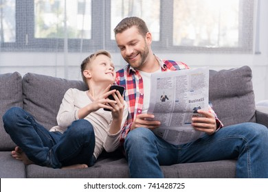 smiling father with newspaper and cute little son using smartphone together at home