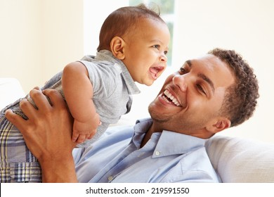 Smiling Father Playing With Baby Son At Home