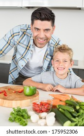 Smiling father showing his son how to prepare vegetables at home in kitchen